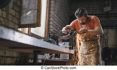 Grinding metal tools with sparkles - forge workshop,...