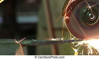 Grinding of metal part with circular saw in the industrial...