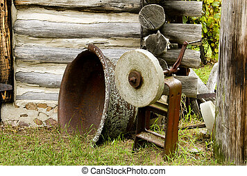 Grinding Stone by a Log Cabin
