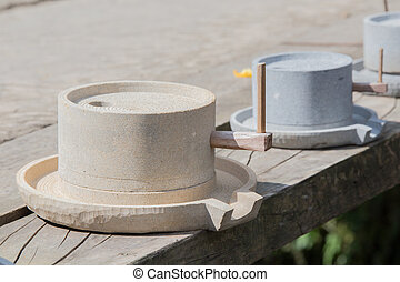 Grinding stone for sale outside on a sunny day