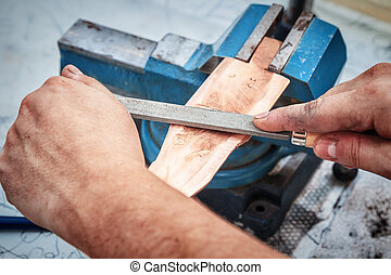 Grinding the copper billet with a file, close up