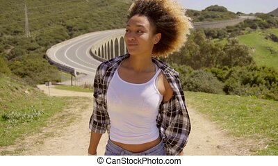 Grinning female walking along dirt road - Beautiful single...