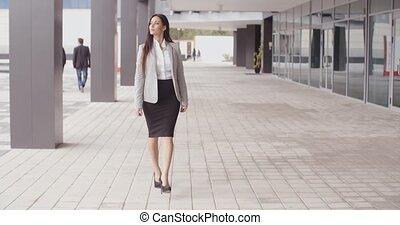 Grinning optimistic professional woman walking - Beautiful...