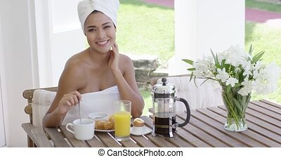 Grinning woman at breakfast table outdoors - Grinning...