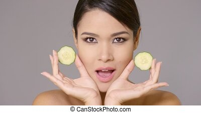 Grinning woman holding cucumber slices - Front view on bare ...