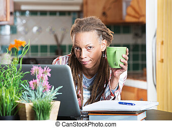 Grinning woman in kitchen with homework and laptop