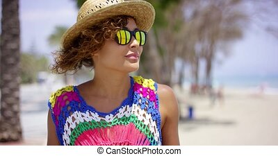 Grinning woman in sunglasses and hat near ocean