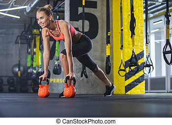 Grinning woman is enjoying crossfit indoors - Smiling ripped...