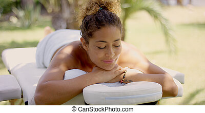 Grinning woman on massage table outside