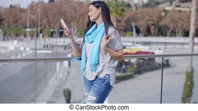 Grinning woman using phone on overpass - Grinning beautiful...