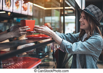 Grinning young woman is receiving meals at cafeteria - ...