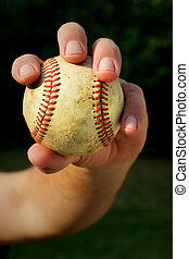 A person's hand gripping an old baseball