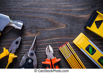 Gripping tongs nippers steel cutter hammer try square construction levels on wooden board close up image maintenance concept.