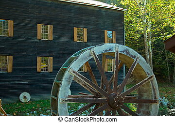 Grist Mill Spare - Water Wheel in front of an Amish Grist...