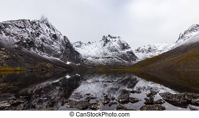Grizzly Lake in Tombstone Territorial Park, Yukon, Canada. Cloudy morning Timelapse. Snow with Autumn Colors. Canadian Rocky Mountain Landscape. Colorful and Vibrant