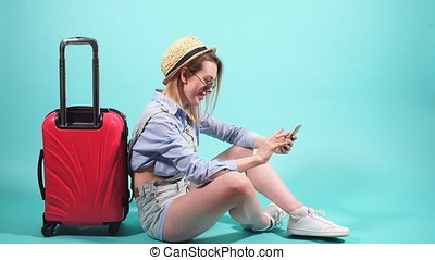 Grl with red suitcase on blue background using smartphone.