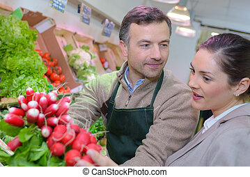 Grocer and customer looking a radishes