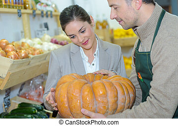 Grocer showing pumpkin to customer
