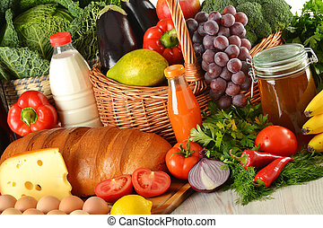 Groceries in wicker basket including vegetables and fruits -...