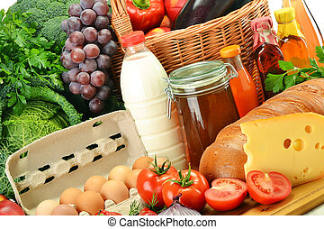 Groceries in wicker basket including vegetables and fruits...