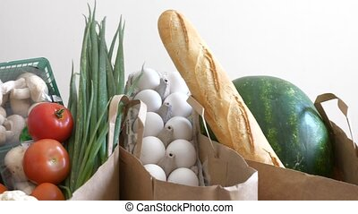 Groceries paper bags filled with variety of fresh products -...