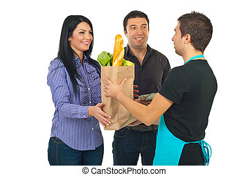 Grocery clerk giving bag to couple - Grocery clerk man...