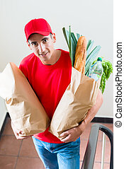 Grocery delivery courier with paper bags of food