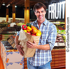 Grocery. - Handsome man with fruits bag in grocery store.