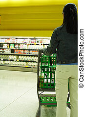 Grocery shopping - A woman shopping for milk at a grocery...