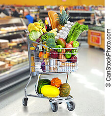 Grocery shopping cart with vegetables and fruits. - Grocery...