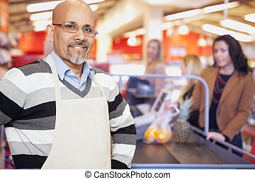 Portrait of a grocery store cashier standing at checkout counter with customers in the background