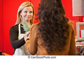 Grocery Store Clerk - Customer holding pineapple with shop...