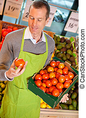 Closeup of a market assistant holding box of tomatoes in the supermarket