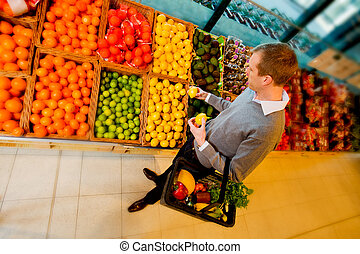 Grocery Store Fruit - A man buying fruit in a grocery store