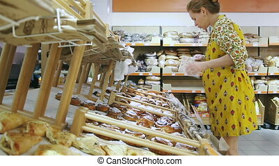 Grocery store: Pregnant woman buying bread at supermarket.