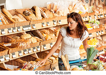 Grocery store: Young woman with shopping cart