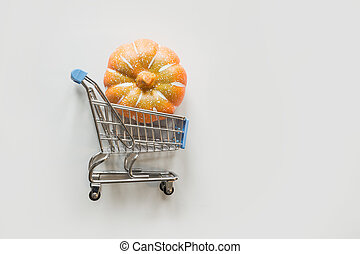 Grocery trolley with pumpkin on grey. Halloween shopping and sale. Flat lay, top view.