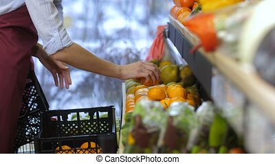 Grocery workers arranging fruits on shop shelves - Close-up...