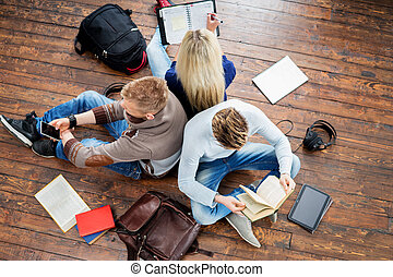groep, van, scholieren, lezende , boekjes , schrijvende , in, notitieboekjes, en, gebruik, een, smartphone, leunend, elkaar, op, houten, floor.