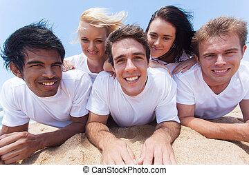 groep van vrienden, het liggen op het strand