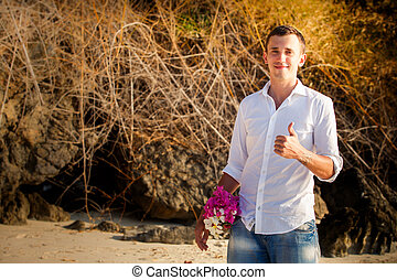 groom against tree roots at beach