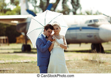 Groom and a bride with an umbrella in the wedding day