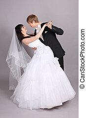 Groom and beautiful bride dance in studio on gray background