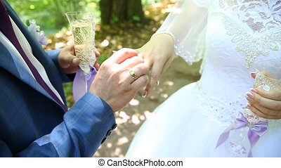 Groom and bride exchange wedding rings, newlyweds exchange rings, Bride puts ring on a finger to her fiance