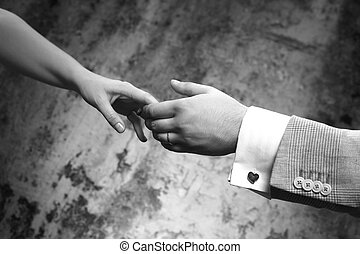 Groom and bride - Female hands in man\\\'s hands on old wall...