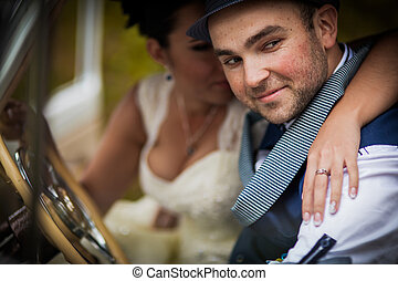 groom and bride in car