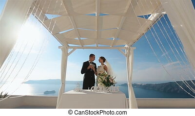 Groom and bride kissing at wedding aisle tent sea background, Santorino close up
