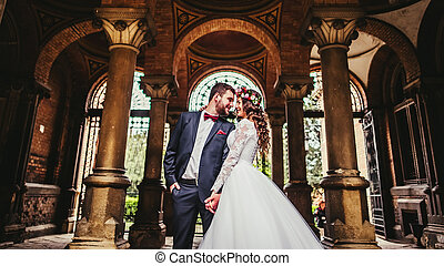 Groom and bride near the columns