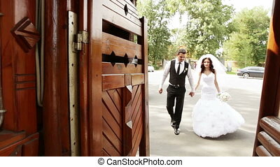 Groom and bride pass in a wooden gate
