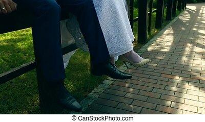 groom and bride sitting on bridge